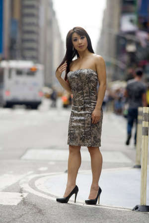 soulful eyes: Asian fashion model strikes a sexy pose on a crowded city street.