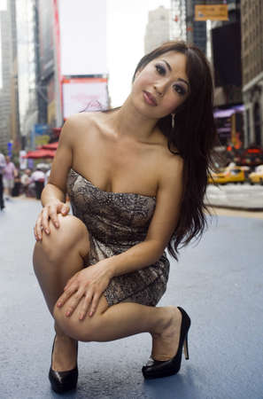 mujer arrodillada: Modelo de moda asi�tica golpea una pose sexy en una calle concurrida de la ciudad. Mucho espacio para la copia!