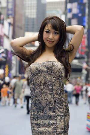 room for text: Asian fashion model strikes a sexy pose on a crowded city street. Stock Photo