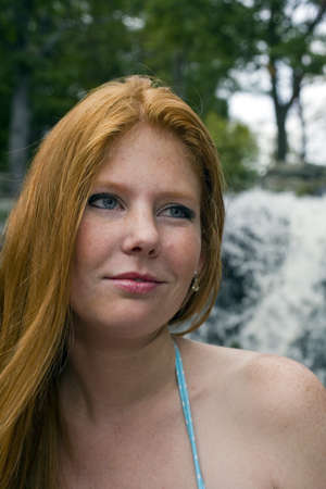 Beautiful redhead gazes off into the distance while sitting outside Stock Photo
