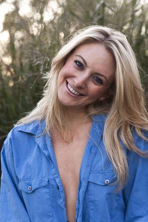 Schöne erwachsene Frau im Freien suchen mit einem großen Lächeln und eines Mannes Hemd aufgeknöpft sexy Standard-Bild - 10884419