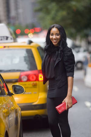 Smiling African-American woman on city street, amidst taxi cabs, with blurred background Stock Photo