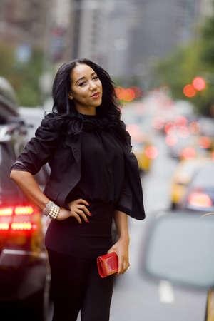 urban colors: Modelo sonriendo desfiles de moda de traje negro con detalles en rojo en el medio de una calle urbana llena de gente.