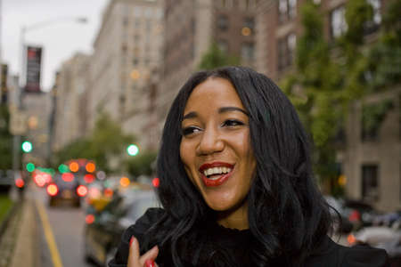 Smiling African-American woman on city street with blurred background