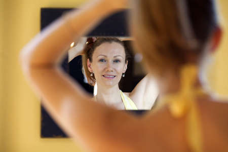 Reflection of mature woman doing her hair in the mirror. Stock Photo