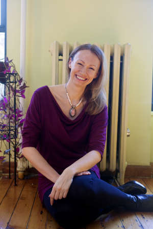 Mature woman laughing while sitting on the floor of her home.