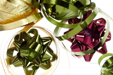 close-up of red, gold and green spools of curling ribbon and bows in seasonal colors.  For gift wrapping