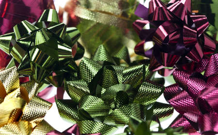 close up of green bow surrounded by gold and red ribbon and bows.  For gift wrapping Stock Photo