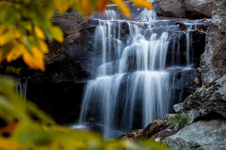 Water rushes over rocks at a secluded country waterfall  Stock Photo