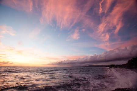 Where land and sea and sky meet   The Indian Ocean runs ashore at Tanah Lot   Tanah Lot is an acient religous site in Bali, Indonesia, Southeast Asia   At sunset Stock Photo