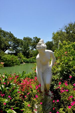 A statue picking flowers by the pond