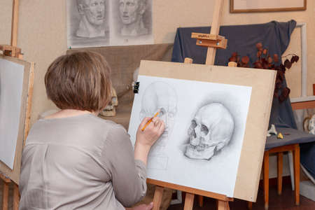 Russia, Surgut, October 17, 2018: Art Studio for adults named after V.Gorda. An adult female student sits at the easel, learning to draw.