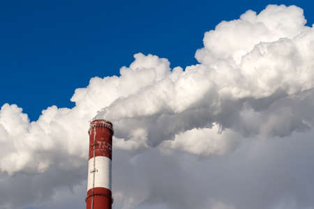 Smoking pipe of a power plant against the backdrop of a clear blue sky.