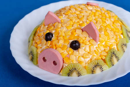 Corn salad in the style of the New year - the year of the yellow pig. Symbol of the new 2019. Salad in the form of a cute pig on a blue background.