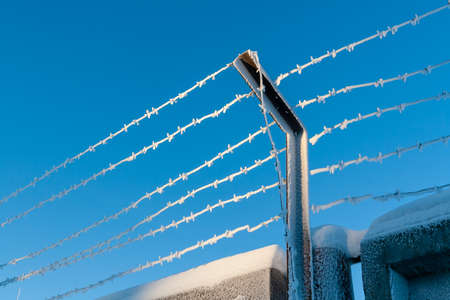 Barbed wire covered with frost, against the blue sky. The restricted area is fenced with barbed wire. Banque d'images - 114808894