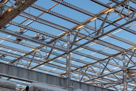 Metallträger an der Spitze der unfertigen Stahlkonstruktion des im Bau befindlichen Gebäudes gegen den blauen Himmel.