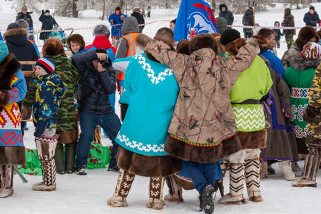 Russkinskaya, Surgut, Russia, 03/23/2019: open traditional holiday of reindeer herders and fishermen, indigenous peoples of Siberia. Photo reporter photographs a group of aborigines in national dress.