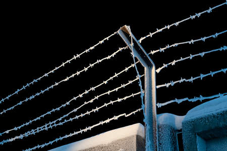 Barbed wire covered in frost, concrete fence covered in frost, isolated on a black