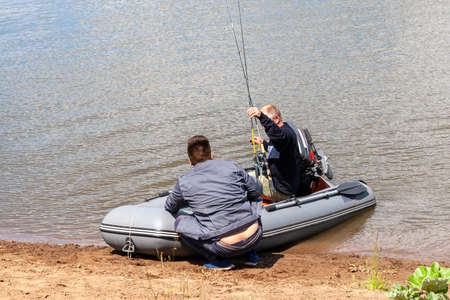 Fishermen are preparing to sail in an inflatable boat with an outboard motor to set off on a fishing trip.