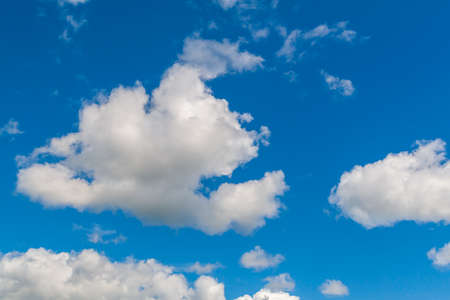 Beautiful whimsical clouds against the blue daytime sky.