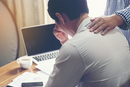 Businessman with hand on shoulder of colleague, consoling businessman suffering from headache in office.