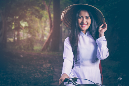 Portrait of beautiful young Asian teen with long hair wearing a costume of Viet Nam (Ao dai) she is currently towed a bicycle and holding a hat by verdant gardens background amid the smog and Sun morning.