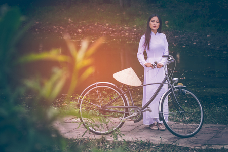 Portrait of beautiful young Asian teen with long hair wearing a costume of Viet Nam (Ao dai) she is currently towed a bicycle and holding a hat by verdant gardens background with copy space. Imagens