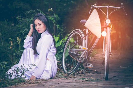 Portrait of young Asian girl with long hair wearing a dress of Vietnam (Ao Dai) sitting beside her bike, and hats woven palm leaves hanging on bicycle handlebars. Set amidst the lush gardens with copy space.