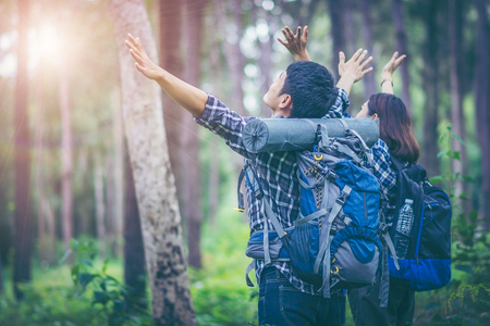 Surrounded by pine trees, young men and young women hikers Asian standing spreading both arms, which represents freedom. They are travelers who enjoy the adventure. Study the ecology of the rainforest.