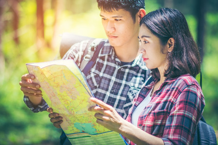 Amid the pine forests, young men and young women hikers Asians are reading a map. They are travelers, adventure lovers of nature. Studying the ecology of rainforests with copy space.