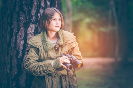 Beautiful girl teen American hikers looking up on the tree. She wore wearing a green sweater with binoculars in the hand. In the warm sunlight in the forest with copy space. Imagens