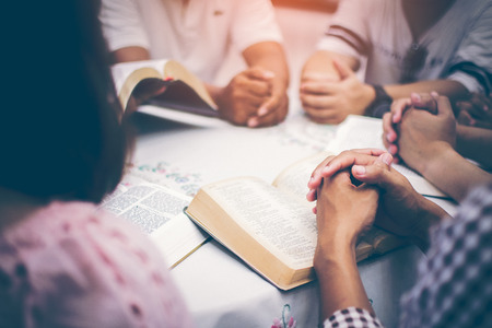 Christians are congregants join hands to pray and seek the blessings of God, the Holy Bible. They were reading the Bible and sharing the gospel with copy space. 스톡 콘텐츠