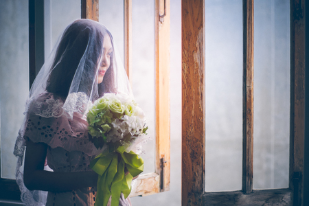 Asian girl wearing a wedding dress holding a bouquet of white roses in front of wooden windows within the Catholic Minster. Her waiting groom with a sense of joy with copy space. Imagens