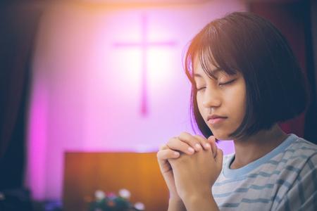 Aziatisch tienermeisje met kort haar. Ze zit in de kerk, de handen en ogen van gebed om zegeningen van de God in elkaar grijpend. De achtergrond is er een kruisbeeld als symbool van Christus met exemplaarruimte. Stockfoto