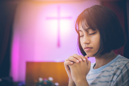Short hair teen girl Asian She is sitting inside the Church, interlocking the hands and eyes of prayer for blessings from the God. Background there is a crucifix as a symbol of Christ with copy space.