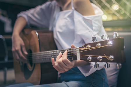 Asian girls wearing white shirts and jeans. She is sitting on a black couch is currently vacationing by playing guitar in a coffee shop. Standard-Bild - 110817259