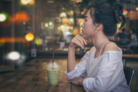 Asian girl sitting in the coffee shop, she vacant and seriously. On a wooden table with a green tea drink in a cool atmosphere, light and colorful with copy space.