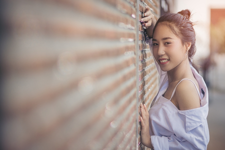 Asian pretty girl standing against the wall brick. She was wearing a white shirt and a sweet smile happily with copy space.