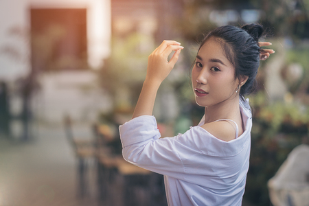 Asian pretty girl. She was wearing a white shirt. Is post posture and look sweet and charming. In an atmosphere of lush trees and the evening sun outside of the coffee shop with copy space. Imagens