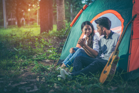 Young Asian couple showing their love by sitting clasped hands and bowed shoulders, showing love while on holiday. His tent on the grass amid the pine forests with evening sunlight. Lifestyle concept. Standard-Bild - 110817287