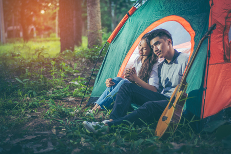 Young Asian couple showing their love by sitting clasped hands and bowed shoulders, showing love while on holiday. His tent on the grass amid the pine forests with evening sunlight. Lifestyle concept.
