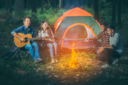 A group of tourists trekking Asians sitting in front of the tent all while relaxing camping by playing the guitar and made a fire from the firewood within the pine forest and the night atmosphere.