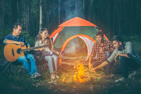 A group of tourists trekking Asians sitting in front of the tent all while relaxing camping by playing the guitar and made a fire from the firewood within the pine forest and the night atmosphere. Imagens