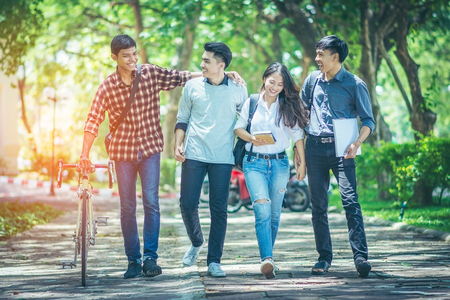 A group of Asian student was walking on the road within the University. They talk to smile happily and motivate the bicycle to walk together. In the shade of trees streets and the sun in the afternoon Imagens
