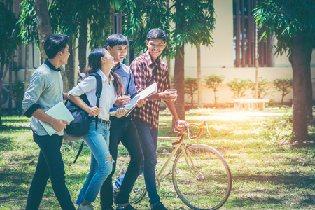 A group of Asian student was walking on the road within the University. They talk to smile happily and motivate the bicycle to walk together. In the shade of trees streets and the sun in the afternoon Standard-Bild - 110817313