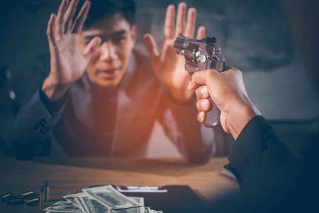 Criminals are aiming at young businessman. Dollar banknotes USD and bullets on the table, The young man hand show signs of surrender and looks scared, concept blackmail, extortion of businesses. Imagens