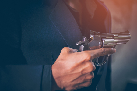 A close-up of a hand, the young man, wearing a black suit, pulling a Revolver out of the Holster under jackets on a dark background. He holding gun in hand. Secret agent, mafia, bodyguard concept.