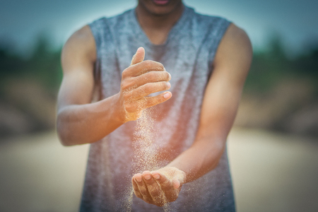Sand running through fingers of the young man. A symbol of lost time and show the countdown to the end of all things in the universe. Deadline, Business and time management concept with copy space. Stock Photo
