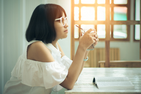 Asian teen girls wearing white shirts and glasses. She is holding a glass of pure water in her hand, showing emotions, thought and vision by reading the books, which are placed on the white table.