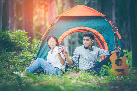 In the pine forest. Asian couples are honeymoon and clink glasses vodka. them sitting in front of the tent and smiled happily. The young man holding the guitar in hand. People and adventure concept.